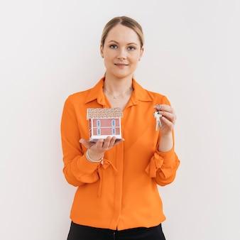 Portret die van vrouw een paar sleutels houden en een modelhuis dat op witte achtergrond wordt geïsoleerd