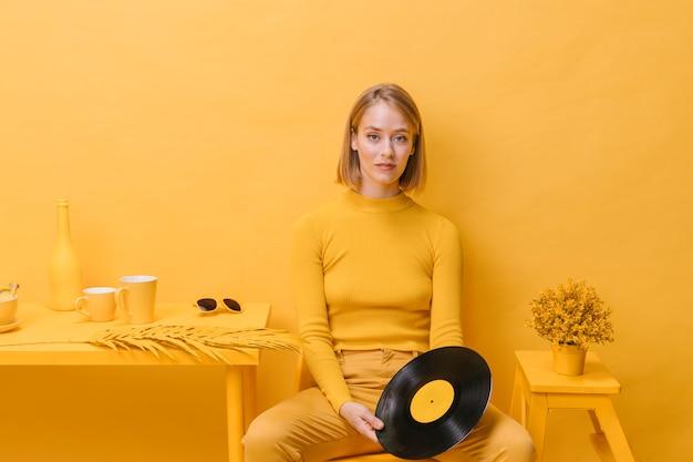 Portret die van vrouw een vinyl in een gele scène houden