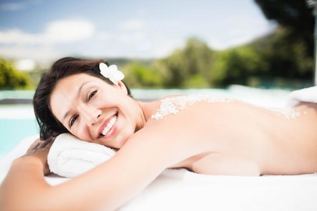 Portret die van vrouw op massagelijst liggen met zout schrobt terug in een kuuroord
