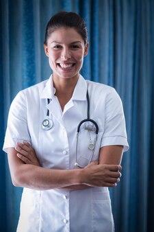 Portret die van vrouwelijke arts zich met gekruiste wapens bevinden