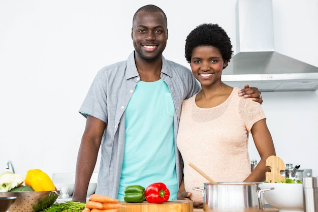 Portret die van zwanger paar elkaar thuis in keuken omhelzen