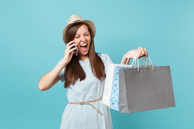 Portret dolblij vrouw in zomerjurk, strohoed met pakketten tassen met aankopen na het winkelen, praten op mobiele telefoon geïsoleerd op blauwe pastel achtergrond. kopieer ruimte voor advertentie.