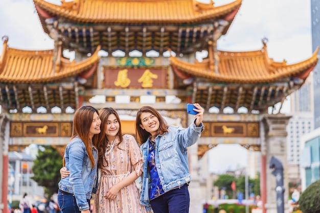 Portret drie aziatische gelukvrouwen die slimme mobiele telefoon voor selfie samen gebruiken, kunming, china