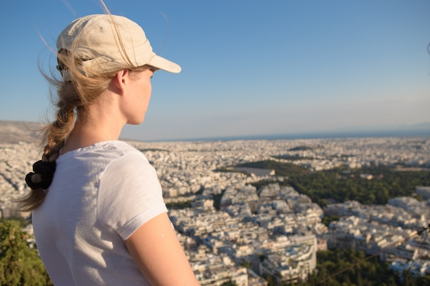 Portret dromerig en lucht aantrekkelijk meisje in een pet speels en zorgeloos met mooie glimlach op zonnige dag van de stad van athene met mount lycabettus, griekenland zoals gezien door de lucht.