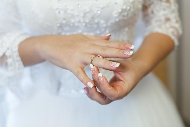 Portret een bruid in witte jurk met gouden trouwring op haar vinger.