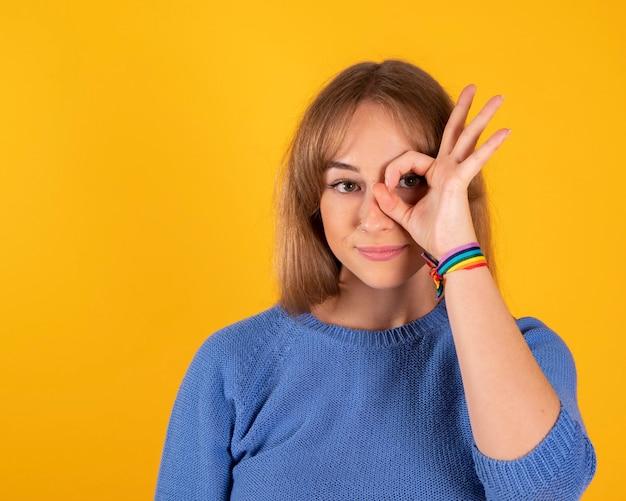 Portret een charmant en gelukkig vrolijk meisje dat het teken van goede en goede keusoplossing toont die op een gele ruimte wordt geïsoleerd