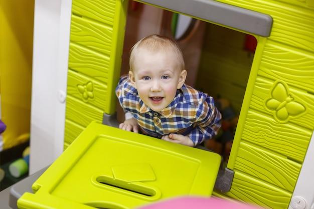 Portret een glimlachend jongensspel in de speelkamer. gelukkig kind in speelgoed huis close-up. rust in het kindercentrum.