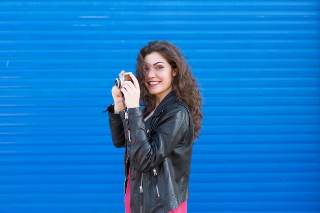 Portret een jonge mooie vrouw die een uitstekende camera over blauw houdt.