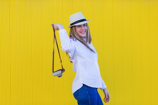 Portret een jonge mooie vrouw die een uitstekende camera over gele muur houdt