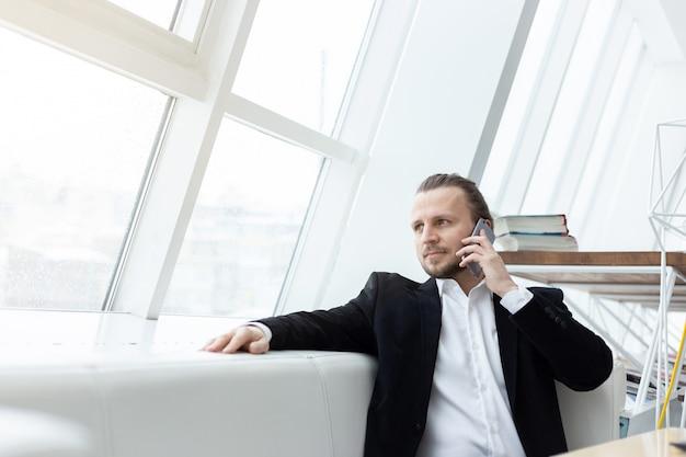 Portret een man in het pak die de mobiele telefoon uitnodigt en op de bank in modern binnenland zit