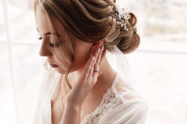 Portret een mooie vrouw in witte jurk corrigeert oorbellen. tedere ochtendbruid. trouwdag. portret van het gezicht van de schattige bruid. gezicht van jonge mooie vrouw met een mooi kapsel en make-up