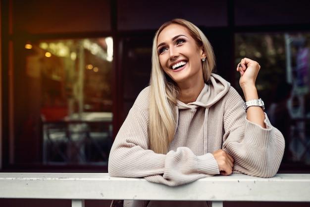 Portret een verbluffende blonde met een sneeuwwitte glimlachstraat