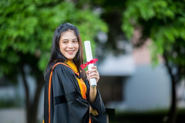 Portret een vrouwelijke afgestudeerde met een universitair diploma met een diploma en plezier