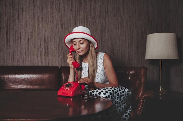 Portret emotie volwassen vrouw actrice met oude rode telefoon poseren gekleed retro styling kleding in vintage woonkamer. vrouw in pin-up fashion stijl zwart-witte jurk in polka dot en hoed