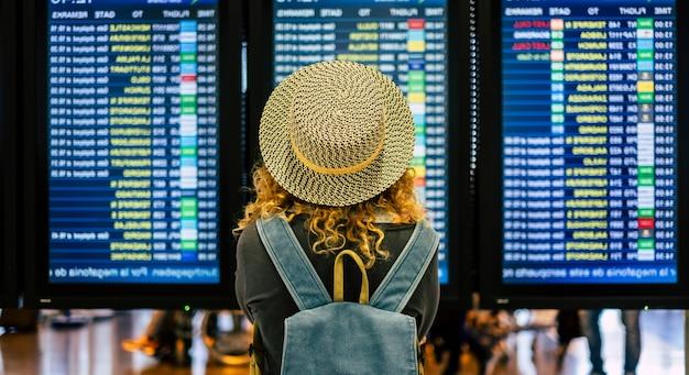 Portret en close-up van de achterkant van een gekrulde vrouw die de tijd van haar vlucht op de luchthaven controleert om buiten te reizen en te genieten van haar vakanties - noamd levensstijl en concept