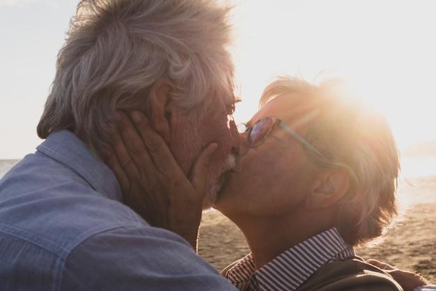 Portret en close-up van twee gelukkige verliefde senioren die lachend dansen met de zon van de zonsondergang tussen hun hoofden
