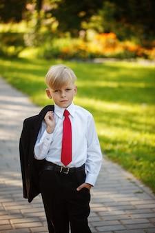 Portret ernstige kleine jongen draagt pak en rode stropdas op aard achtergrond.
