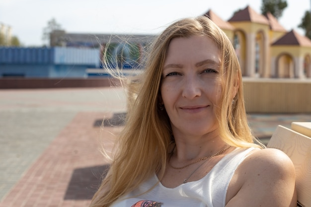 Portret europese vrouw blonde met lang haar lachend buitenshuis op een zonnige dag