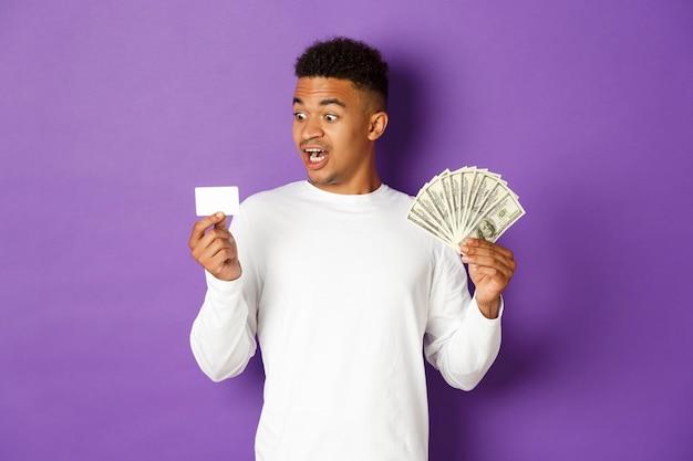Portret expressieve jonge man met creditcard en bankbiljetten