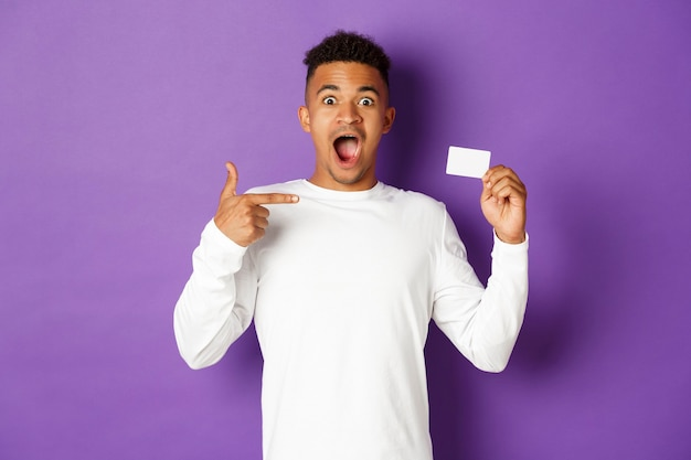 Portret expressieve jonge man met creditcard