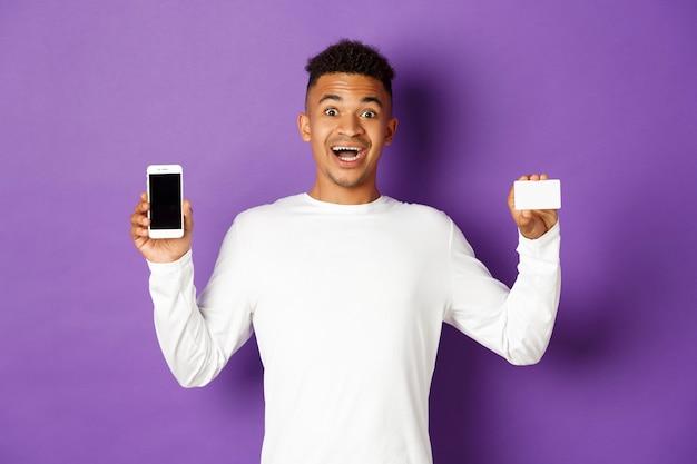 Portret expressieve jonge man met telefoon en creditcard
