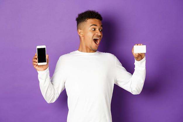 Portret expressieve jonge man met telefoon en creditcard Premium Foto