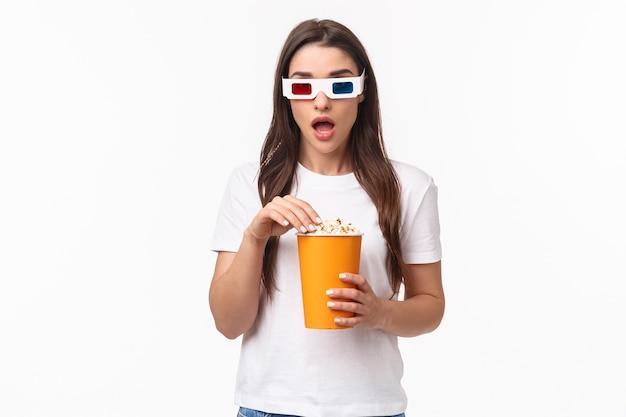 Portret expressieve jonge vrouw die popcorn eet en een 3d-bril draagt