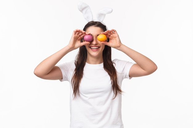 Portret expressieve jonge vrouw draagt konijnenoren en neus, met gekleurde eieren