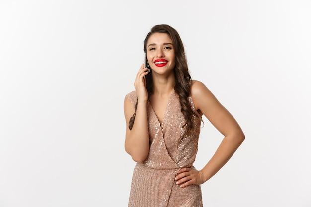 Portret expressieve jonge vrouw in elegante jurk met behulp van telefoon