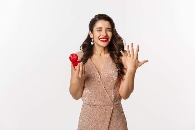 Portret expressieve jonge vrouw in elegante jurk met verlovingsring doos