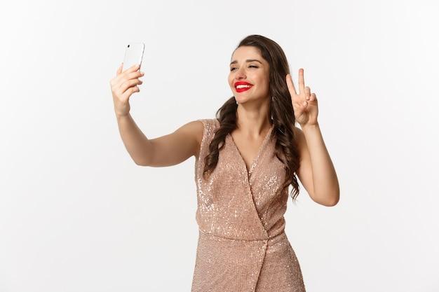 Portret expressieve jonge vrouw in elegante jurk selfie te nemen