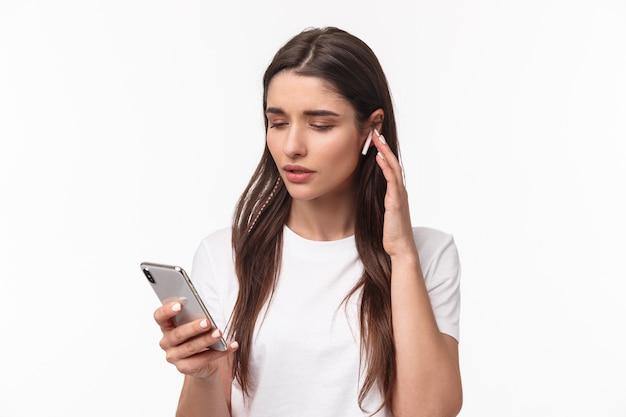 Portret expressieve jonge vrouw met airpods en mobiel