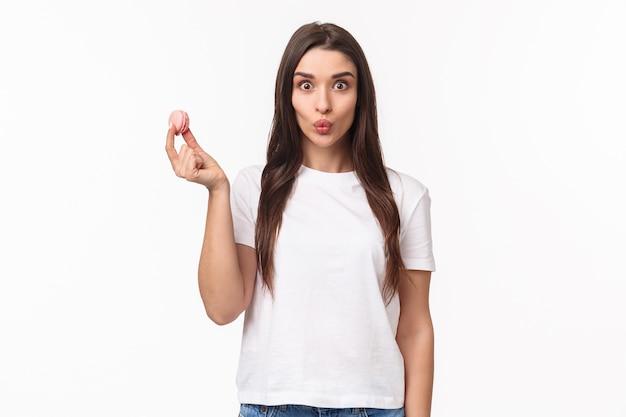 Portret expressieve jonge vrouw met smakelijke twee macarons over de ogen