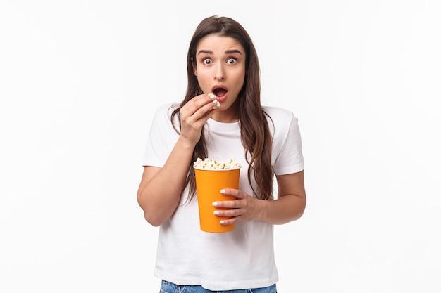 Portret expressieve jonge vrouw popcorn eten