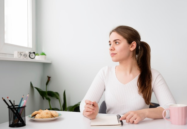 Portret freelance vrouw die thuis in agenda werkt