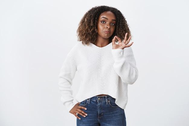 Portret geamuseerd afro-amerikaanse vrouwelijke try-out product show oke ok bevestiging gebaar, mee eens als interessant concept, onverwachte goede resultaten, staande witte muur