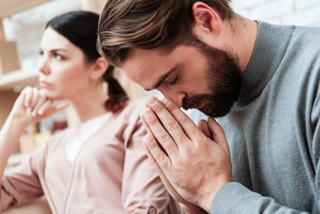 Portret gebaarde man bidden wazig vrouw binnen