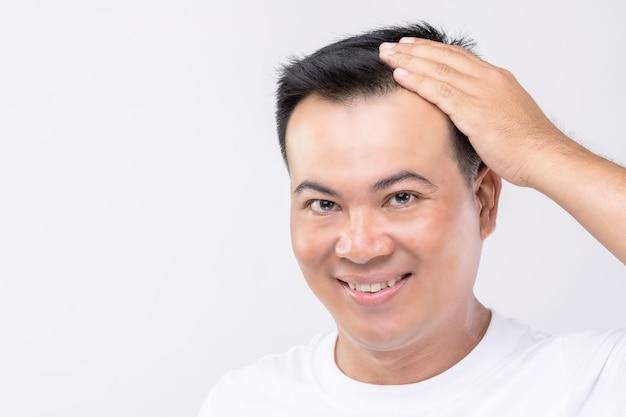 Portret gelukkig aziatische man raakt op zijn hoofd om kaal hoofd of kaal probleem te tonen. studio shoot met kopie ruimte met grijze muur