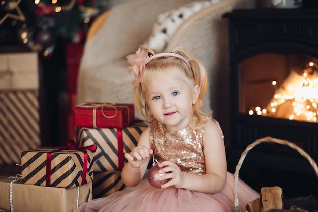Portret gelukkig klein schattig meisje in glanzende feestelijke jurk poseren bij kerstmis interieur middelgroot schot. glimlachend mooie europese vrouwelijke baby kijken camera omringd door de doos van de gift van kerstmis en sneeuwvlokken