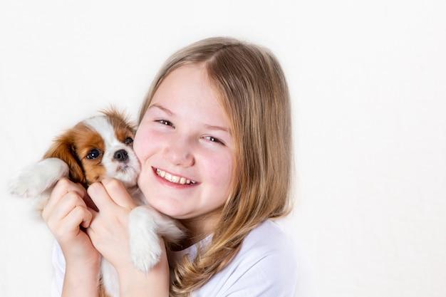 Portret gelukkig meisje die leuke rasechte puppy arrogante koning charles spaniel houden