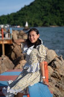 Portret gelukkige aziatische vrouw toerist zit op brug met uitzicht op zee bij pagode in de zee in winderige dag