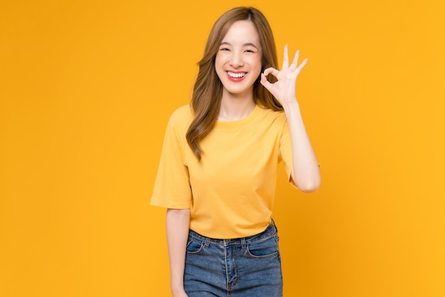 Portret gelukkige aziatische vrouw toont ok teken en kijken naar de camera op gele achtergrond.