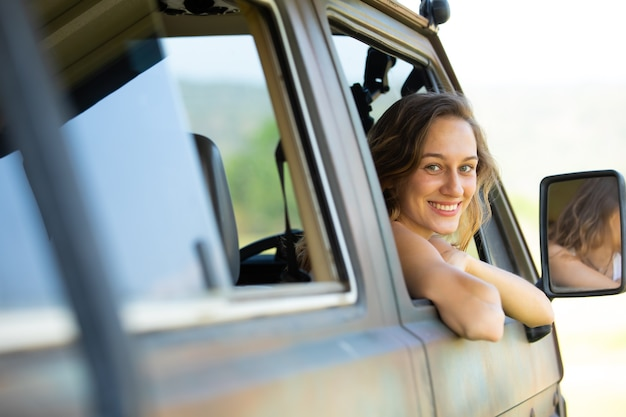 Portret gelukkige blanke vrouw drijft een oude vintage kampeerauto op weg.