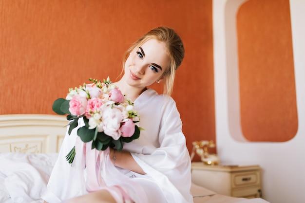 Portret gelukkige bruid in witte badjas op bed in de ochtend. ze houdt een boeket bloemen in handen