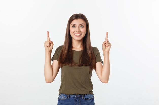 Portret gelukkige en verraste jonge dame status geïsoleerd over grijze achtergrond. kijkend camera wijzend.