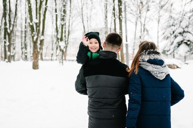 Portret gelukkige familie teruglopen in de sneeuw. vader moeder en kinderen jongen, zoon lopen in winter park.