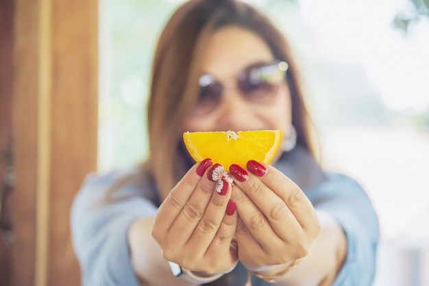 Portret gelukkige jonge aziatische dame die oranje eet