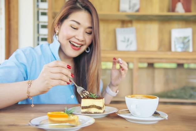 Portret gelukkige jonge aziatische dame in koffiewinkel