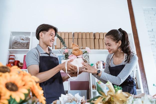 Portret gelukkige jonge bloemist staande verpakking geschenkdoos met vriend in bloemenwinkel