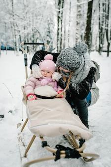 Portret gelukkige jonge moeder met dochter, staan met baby in slee buitenshuis, op de achtergrond winter.
